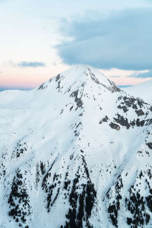 pyramid peak: Pyramid Shaped Mountain Peak Covered in Snow at Sunrise Stock Photo