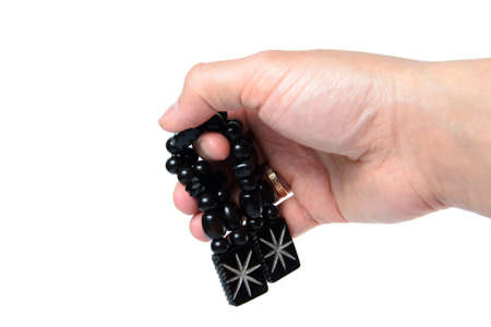 Rosary in hand on a white background isolated. Stock Photo