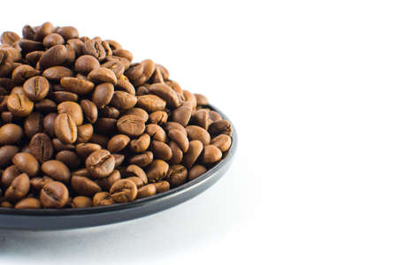 grained: Coffee beans in a small plate on a white background. Isolated