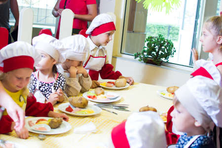 Alchevsk, Ukraine - July 16, 2017: Childrens master class on cooking potatoes in the oven with ham and cheese. Editorial