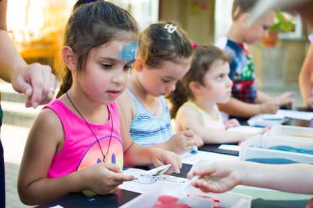 Alchevsk, Ukraine - July 27, 2017: Children paint with glue and colored sand. Childrens party - Editorial