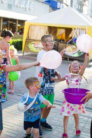Alchevsk, Ukraine - August 3, 2017: Childrens party- catch soap bubbles-