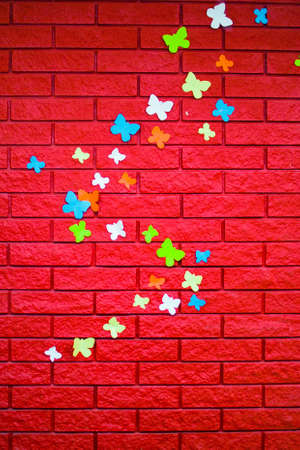 red brick wall with pasted paper butterflies Stock Photo