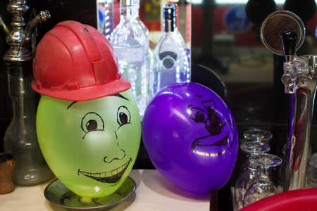 inflatable balls with faces with a helmet in the bar. Stock Photo