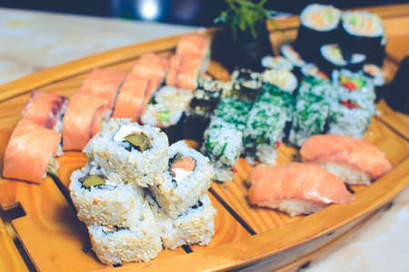 many kinds of sushi on a wooden stand in the form of a ship