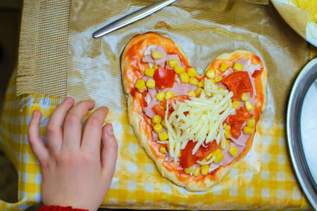 children cook pizza from raw ingredients with their own hands
