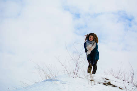 girl in winter stands on a hill