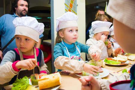Alczewsk, Ukraina - 8 listopada 2018: dzieci w postaci kucharzy przygotowują kanapki.