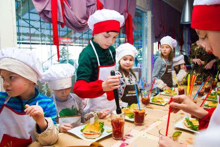 Alchevsk, Ukraine - 8. November 2018: Kinder in Form von Köchen bereiten Sandwiches vor.
