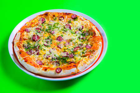 hot tasty fresh pizza on a plate close-up. green background