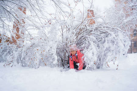 child plays in the snow in a park near a snowy bush.