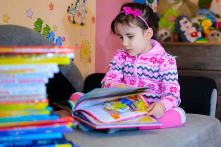 Cute girl on the background of her toys with a book.