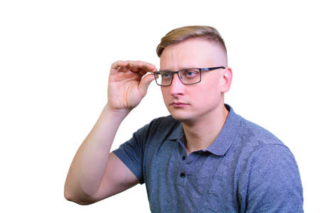 Portrait of a cheerful young guy adjusts his glasses. isolated on white background.
