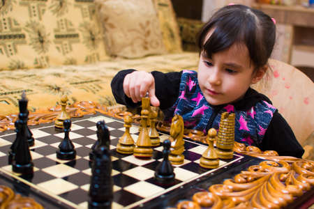cute girl playing chess at home with her grandfather. Banque d'images