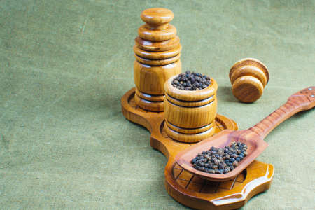 set of small wooden barrels for storing spices next to a wooden spatula with seeds of pepper