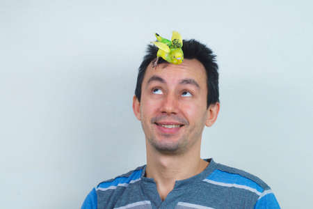 Cool budgie. A cute yellow budgie is sitting on the head of a young man.