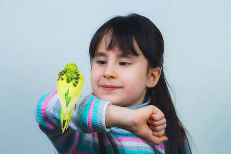 the child plays and communicates with his green hand-wavy parrot