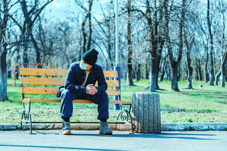 medical mask as protection against coronavirus. guy sits alone on a bench violating the exit ban