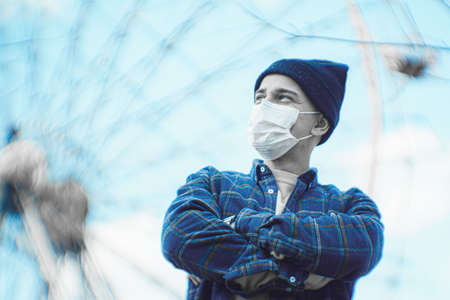 mask as protection against coronavirus. guy on the background of an empty ferris wheel. concept of loneliness