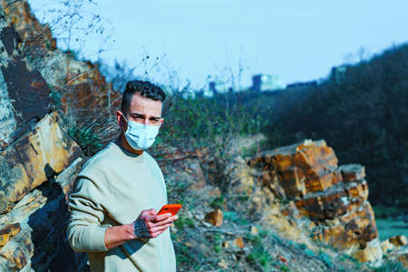 medical mask as protection against coronavirus. guy in the mountains isolated from coronavirus.