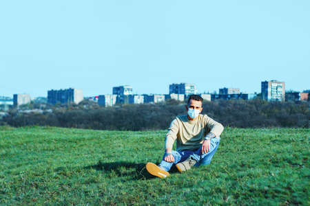 medical mask as protection against coronavirus. guy sits in a clearing away from the city hiding from the coronavirus. concept of loneliness