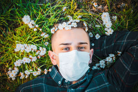 medical mask as protection against coronavirus. guy lies on grass around early spring flowers. concept of loneliness Banque d'images