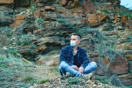 medical mask as protection against coronavirus. guy in the mountains isolated from a pandemic. self isolation concept Banque d'images