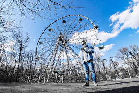 medical mask as protection against coronavirus. guy on the background of an empty ferris wheel in the park alone