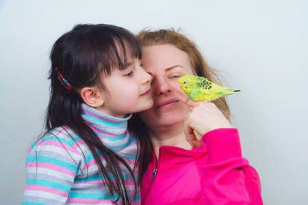 mother and daughter communicate with their tame yellow parrot. Tamed Pet