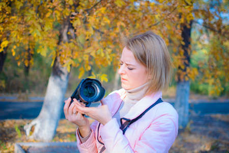 A young girl photographer walks through the forest and takes pictures of nature on a dslr camera Banque d'images