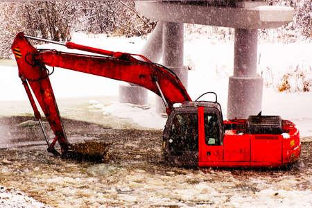 strengthen: Hard work. Carrying excavator repairs to strengthen the shore near the bridge
