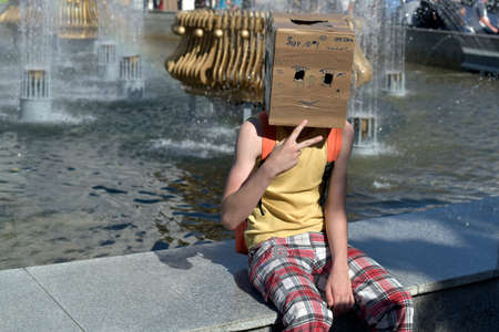 painted face: Teenager dressed on a head box with carved eyes and painted face Stock Photo