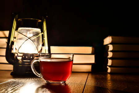 The light of a kerosene lamp, cup of tea and books on the table
