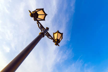 Lamppost against the background of the sky with clouds close-up