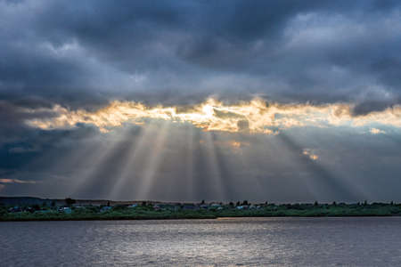 Beams of setting sun make the way through clouds over the river