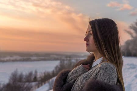 Girl with long straight hair in a fur coat against the background of a winter evening sky