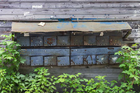 Old mailboxes on a wooden wall of a residential building close up 版權商用圖片