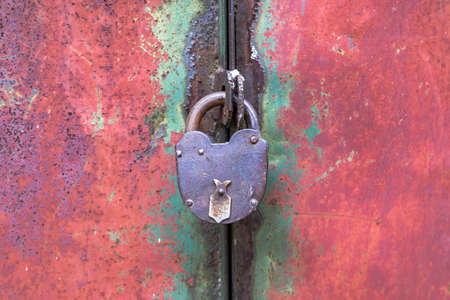 Closed on an old padlock metal door leaf close up 版權商用圖片