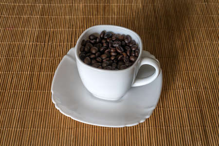 Roasted coffee grains in a white cup standing on a saucer close up 版權商用圖片