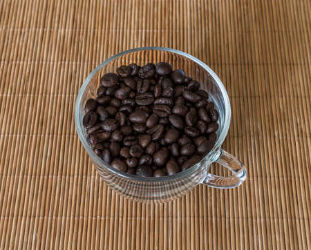 Roasted coffee beans in a transparent glass cup standing on a straw napkin