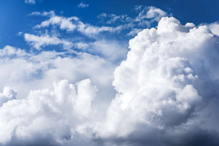 White cumulus clouds floating on a blue sky close up