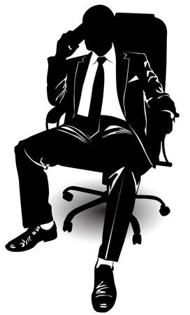 A man in a business suit talking on a cell phone while sitting on an armchair