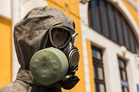 Mannequin head with a gas mask and a hood of a protective clothing set close up