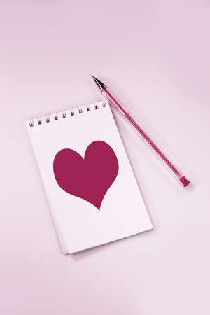 Notebook with a heart on a pink background