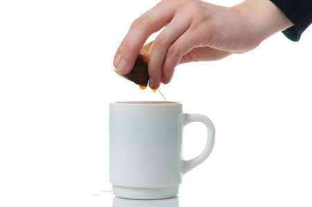 Hand wringing out tea bag in a mug on white background