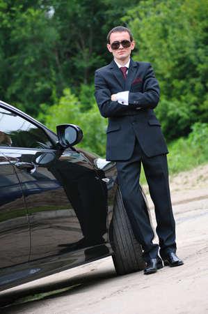 高価な車の近くに黒のメガネとスーツのスタンドと若い男