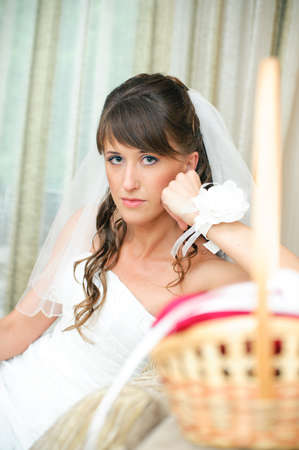 pensive bride in a white dress looking at camera Stock Photo