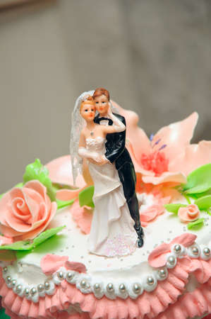 Embracing wedding couple. Figures on a cake