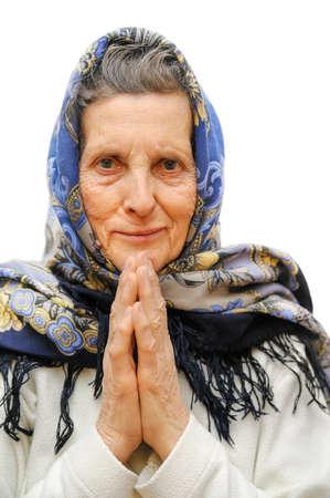 vejez: mujer de edad avanzada rezando en el fondo blanco Foto de archivo