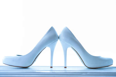wedding shining shoes with a high heel on a white backgrounds  illuminate from blue lamp opposite windows light